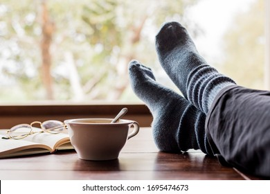 cup of coffee and a book with legs resting on a table