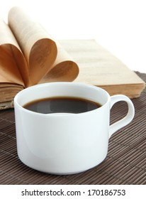 Cup of coffee and book on bamboo mat on white background