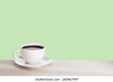 Cup of coffee and a book on a wooden table