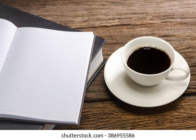 Cup of coffee with books and note book on old wood table