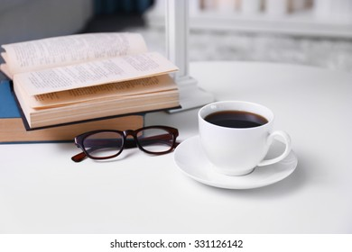 Cup of coffee with books on table in room