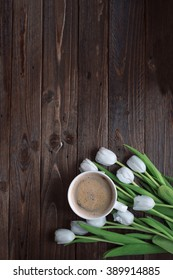 A cup of coffee, a bouquet of white tulips on a dark wooden table. Top view.