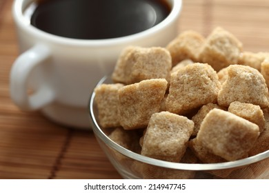 Cup of coffee and brown cane sugar in a glass bowl on bamboo napkin.