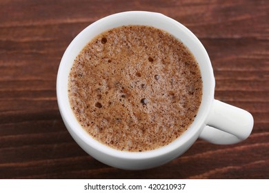 Cup of coffee with brown foam on wooden background, top view