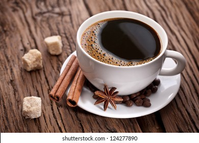 Cup of coffee with brown sugar on a wooden table.