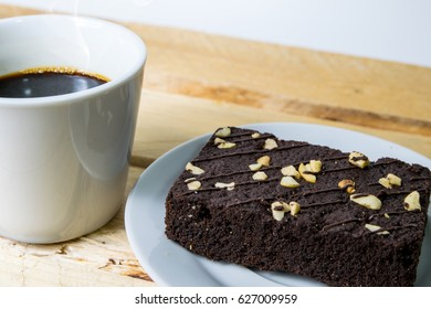 Cup of coffee and  brownie on wooden table