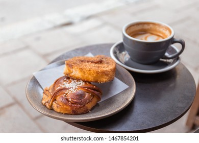 Cup of coffee and bun with cinnamon lying on the table in cafe in a street