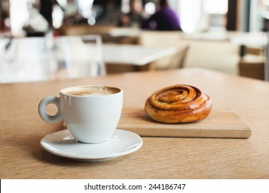 Cup of coffee and bun with cinnamon lying on the wooden table in cafe