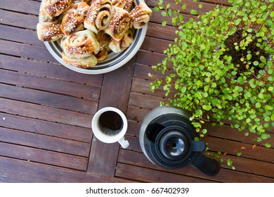 Cup of coffee, buns and green flower are on the table. Bird view