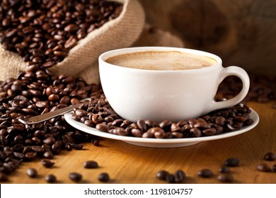 cup of coffee and  cake on coffee beans.