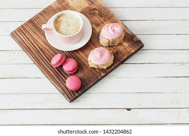 cup of coffee with cakes on white wooden background