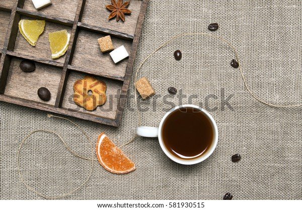 Cup of coffee, candies, coffee beans on linen background