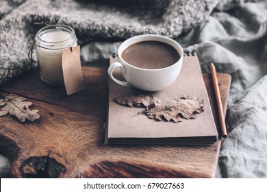 Cup of coffee and candle on rustic wooden serving tray with blanket. Spending autumn weekend in the cozy bed.