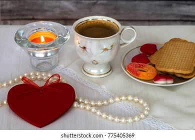 A cup of coffee, candy and heart-shaped pearl necklace on a wooden table. Valentine's Day.