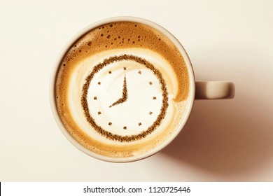 a cup of coffee cappuccino with a clock pattern from cinnamon on milk foam