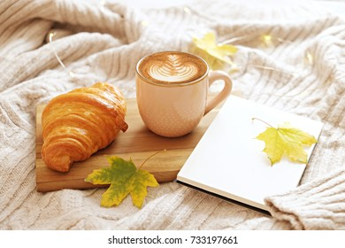 A cup of coffee cappuccino, croissant and autumn leaves on knit sweater with light bulb. Autumn decor, fall mood, autumn still life. Hugge concept