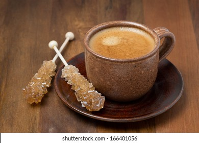 cup of coffee and caramel sugar on sticks, close-up