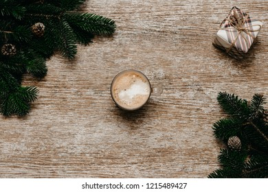 A cup of coffee in the center beside gift box and spruce branches on the wooden table. Top view