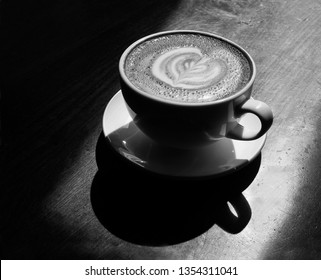 Cup of Coffee in a Ceramic Cup on a Wooden Table in a shaft of Sunlight