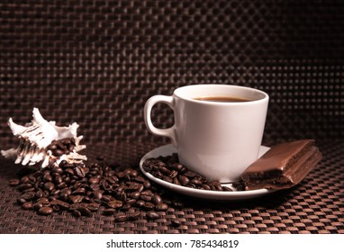 A cup of coffee with a chocolate bar, scattered coffee beans and a shell.