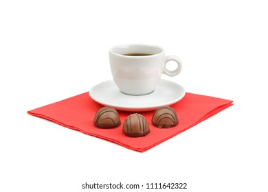 A cup of coffee and chocolate candies on a red paper napkin isolated on white background.