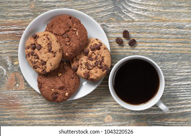 Cup of coffee and chocolate chip cookies in plate on old wooden table, top view
