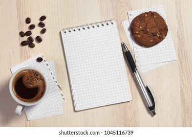Cup of coffee with chocolate cookie, notebook and pen on light wooden table. Top view with space for text