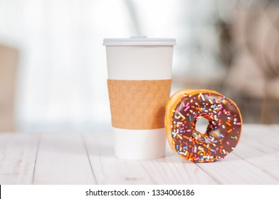 Cup of coffee and chocolate donut on wood table. Coffee break with donuts.
