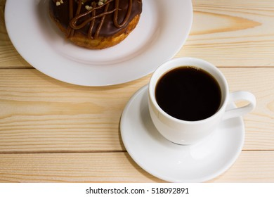 Cup of coffee with chocolate donuts