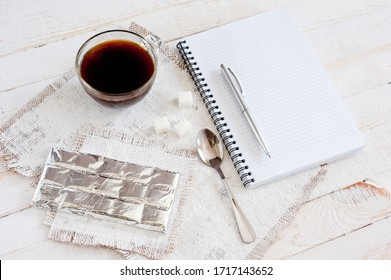 A cup of coffee, chocolate, a sheet of paper and a pen on a white wooden surface. Background for work at home in quarantine. The difficulty of adapting work at home.
