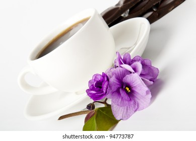 cup of coffee, chocolate and violets on a white table