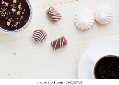 cup of coffee, chocolates, meringue, a cottage cheese dessert of handwork on a wooden background the top view