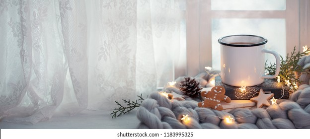 Cup of coffee with Christmas lights near window