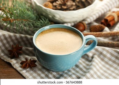 Cup of coffee and Christmas tree branch on napkin, closeup