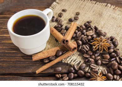 cup of coffee with cinnamon and anise stars on a dark wooden background