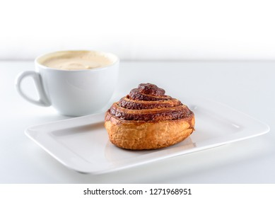 Cup of coffee and cinnamon roll bun pastry over the white background