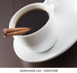 Cup of coffee with cinnnamon on the wooden background