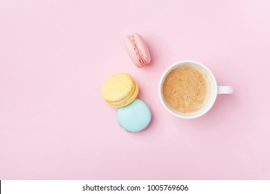 Cup of coffee and colorful macaron on pastel pink background top view. Cozy breakfast. Fashion flat lay. Sweet macaroons.