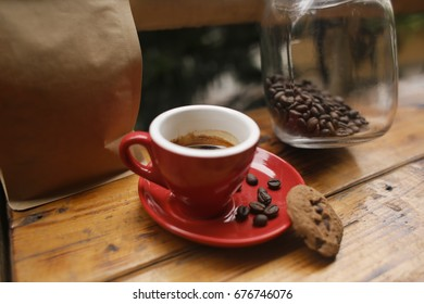 A cup of coffee with cookie and bottle of coffee beans