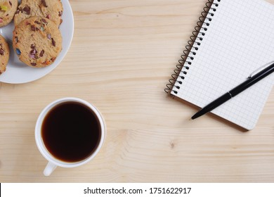 Cup of coffee, cookies and notebook with pen on wooden background, top view