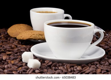 cup of coffee and cookies on beans on black background