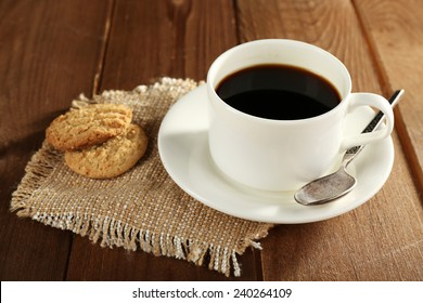 Cup of coffee with cookies on burlap cloth on wooden table background