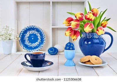 Cup of coffee and cookies on light wooden table with red tulips and springtime decorations