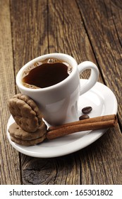 Cup of coffee and cookies on a wooden table
