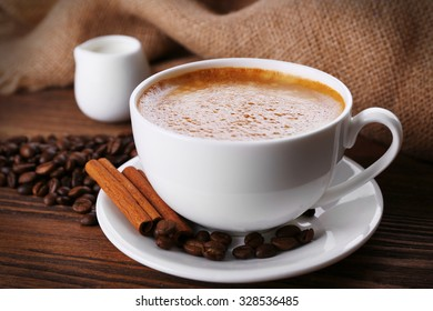 Cup of coffee with cream and coffee beans on wooden background