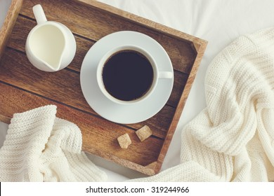 cup of coffee, cream and brown sugar on wooden tray, toned,  top view