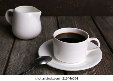 Cup of coffee and cream in milk jug on wooden table on dark background