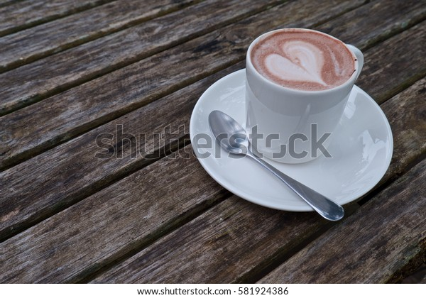 A cup of coffee with cream on wood table
