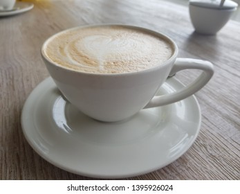 Cup of coffee with cream on wooden background