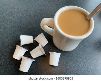 A cup of coffee with cream and single serving coffee creamer packages.